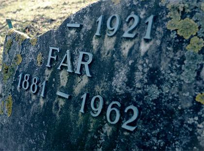 En gammal sleten gravsten med inskriptionen far.