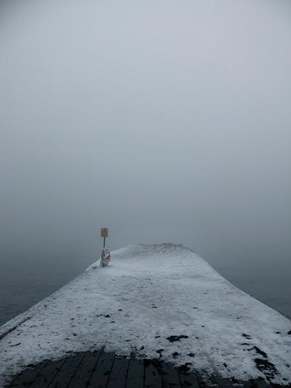 En snöig brygga när dimman ligger som tjock gröt över havet