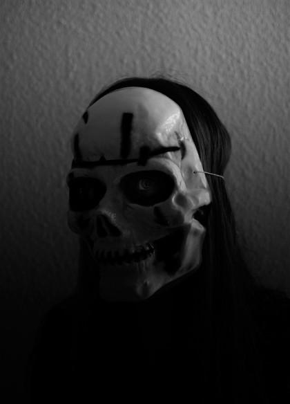 En person med döskalle mask för ansiktet.