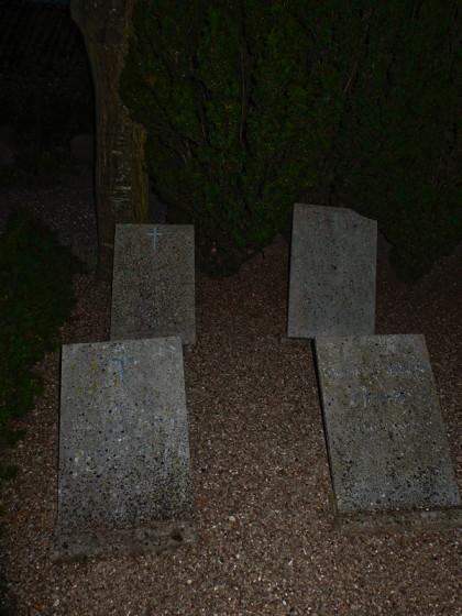 Fyra gravstenar på en mörk kyrkogård.
