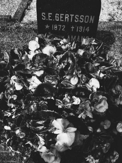 Gravsten på Nättraby kyrkogård med en massa blomster framför