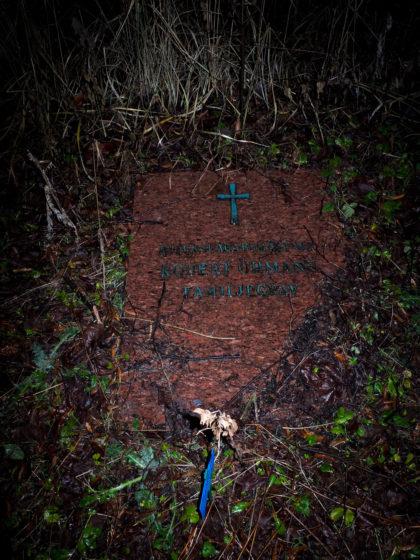 Övergiven gravsten övervuxen med gräs och ogräs.